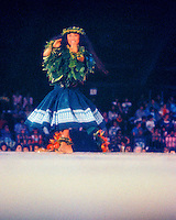 Merrie Monarch Hula Festival kahiko (ancient dance form) winner Lisa Doi, smiles as she dances on the stage before a large crowd.