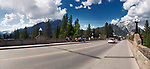 Sunny panoramic street scenery of people on Banff Avenue bridge in the Town of Banff in Alberta Rockies with Rocky Mountains in the background. Alberta, Canada 2017
