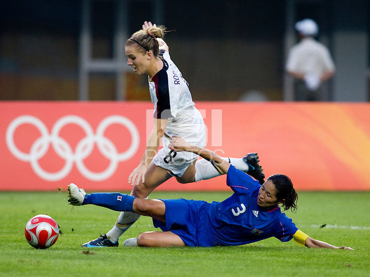 USWNT forward (8) Amy Rodriguez steps through the tackle of Japanese captain (3) Hiromi Ikeda  while playing at Qinhuangdao Stadium. The US defeated Japan, 1-0, during first round play at the 2008 Beijing Olympics in Qinhuangdao, China.