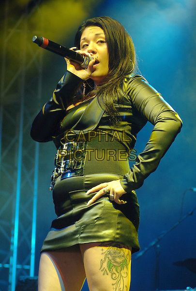 MUTYA BUENA.performing live at the 2007 V Festival, Hylands Park, Chelmsford, Essesx, England,.19th August 2007..half length live music on stage gig concert rose tattoo on leg thigh black top belt mini skirt microphone hand on hip.CAP/ BEL.©Tom Belcher/Capital Pictures.