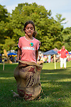 Old Bethpage, New York, USA. September 28, 2014. A young girl is participating in the Children's Sack Race, at the 172nd Long Island Fair, a six-day fall county fair held late September and early October. A yearly event since 1842, the old-time festival is now held at a reconstructed fairground at Old Bethpage Village Restoration.