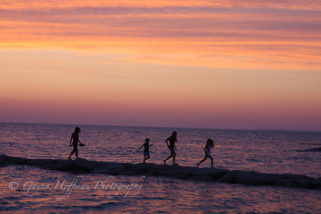 Children running along jetty at sunset. Rock Harbor, Orleans, MA