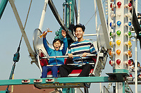 VIETNAMESE BROTHERS RIDE THE FERRIS WHEEL AT TET FESTIVAL MIDWAY. VIETNAMESE-AMERICAN BROTHERS. SAN JOSE CALIFORNIA USA.