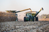 63801-06701 John Deere combine harvesting corn while unloading corn into wagon, Marion Co., IL