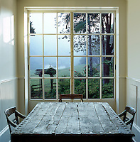 Views across an antique studded table through traditional French windows out to a misty landscape