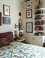 The bedroom has a retro feel with the richly embroidered cushions on the bed, a crewel bedspread bought from a thrift shop and the vintage wall light over the bedside chest of drawers. An arrangement of built-in cupboards and shelving allows storage and the display of various items. The walls are painted in Donald Kaufman Color's DKC-43.