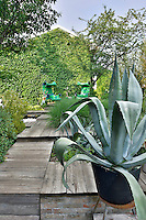An agave plant grows in a pot beside a decked pathway that leads to a sitting area where two green chairs sit side by side.