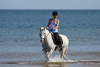 Holkham, Norfolk, England, 03/08/2009..Two women riding horses on Holkham beach.