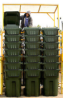 A worker inspects plastic garbage cans prior to being shipped out SSI Schaefer plastic manufacturing in Charlotte, NC.