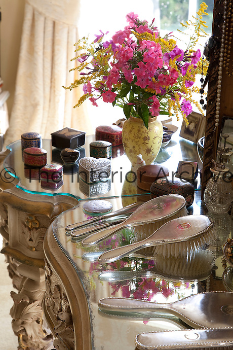 An array of brushes, boxes, mirrors and bottles sit on the dressing table, their silver surfaces glimmering in the glass table-top