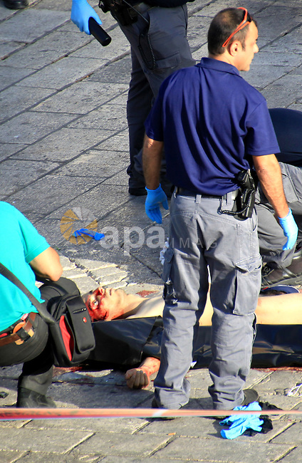 "Israeli security forces and forensic police inspect the body of a man who attempted to carry out a knife attack at the Damascus Gate at the entrance of the Old City in east Jerusalem on October 14, 2015. Israeli police said a ""terrorist"" attempted to stab a security guard at an entrance to Jerusalem's Old City but was shot before harming anyone, the latest in a wave of such incidents. Photo by Mahfouz Abu Turk"