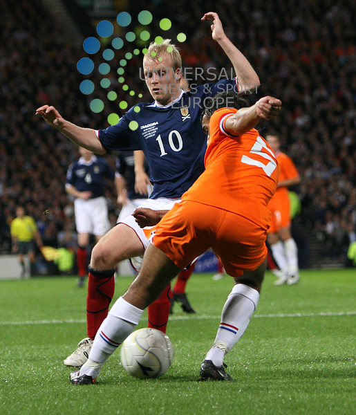 Scotland's Steven Naismith in a challenge with Hollands Giovanni van Bronckhorst during the 2010 Fifa World Cup South Africa Qualifier Group 9 Match between Scotland and Holland at Hampden Park Glasgow. 09/09/09....Picture by Ricky Rae/ Universal News & Sport (Scotland).