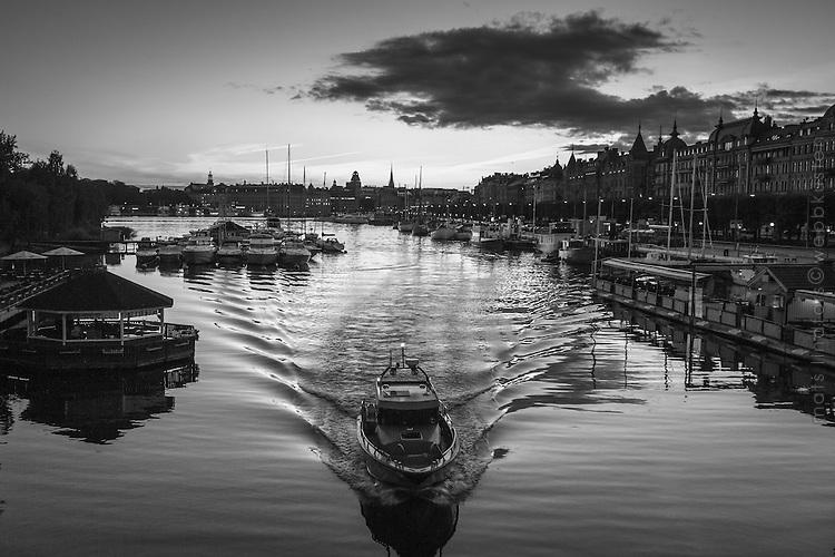 Seascape from Stockholm, Sweden. Motorbåt i spegelblank skymning vid Djurgårdsbron i Stockholm svartvitt