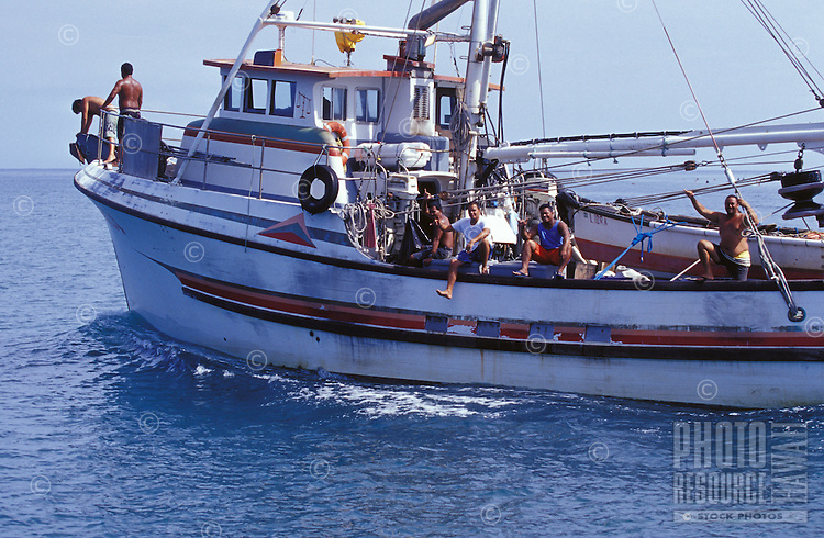 Local working fishing boat crew heading out of port, with smiles, aloha, and shaka signs