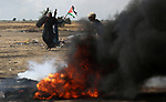 A Palestinian woman burns tires during clashes with Israeli security forces in tents protest where Palestinians demanding the right to return to their homeland, at the Israel-Gaza border, in Khan Younis in the southern Gaza Strip, on May 11, 2018. Photo by Ashraf Amra