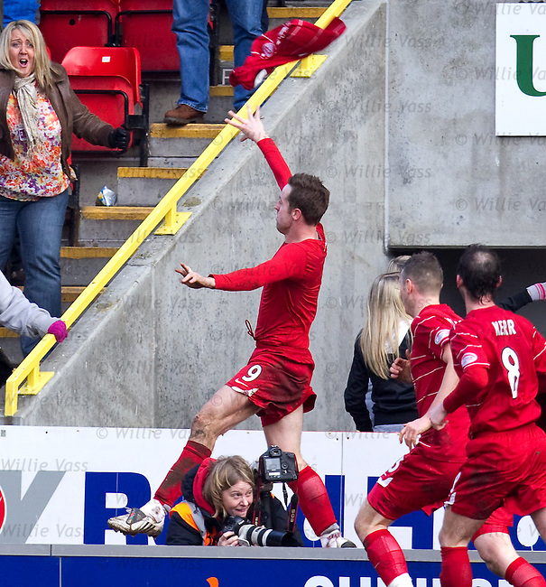 Steven MacLean celebrates his last gasp equaliser for Aberdeen as he jumps over a shocked photographer