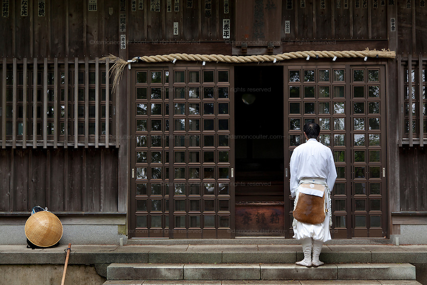 A mountain aesthetic prays at Oyama shrine before his climb of Mount Oyama, Isehara, Kanagawa, Japan Tuesday May 6th 2014