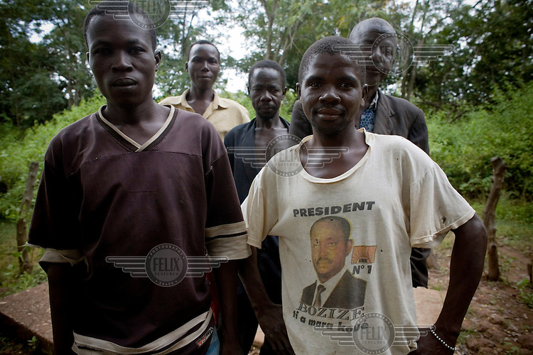 Five men, one wearing a political T shirt of President Bozize, gather in a village.