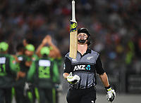 Colin Munro throws his bat in the air as he heads back to the dressing room after being dismissed LBW by Mohammad Amir.<br />