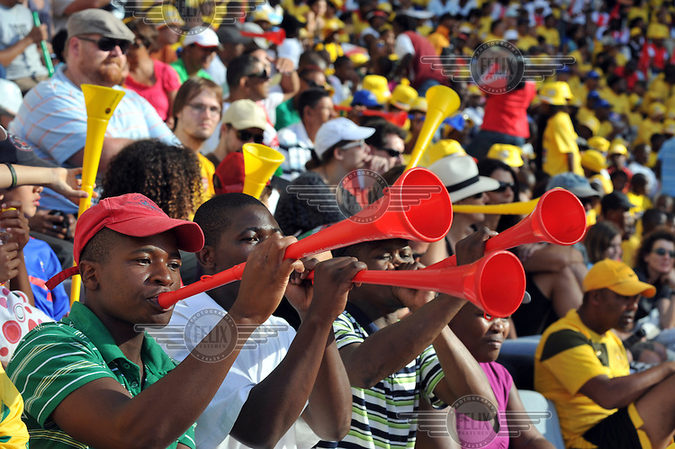 Fans blow vuvuzelas (plastic horns), a staple of South African football, at the opening match at Cape Town's new 2010 FIFA World Cup football stadium. 20,000 fans flocked to the stadium for its first public event since completion in December 2009. The stadium seats 68,000 and the first test event was used to check that all systems, transport, security, staffing and logistics worked satisfactorily.