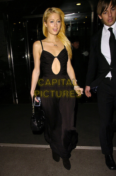 PARIS HILTON.At the Hilton Hotel on Park Lane, London, England,.November 11th 2006..full length black dress steps peep hole cut out hand .Ref: CAN.www.capitalpictures.com.sales@capitalpictures.com.©Can Nguyen/Capital Pictures