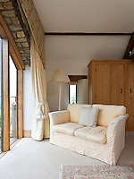 In the master bedroom a cream sofa covered is placed in front of the French windows to take advantage of the views of the surrounding countryside