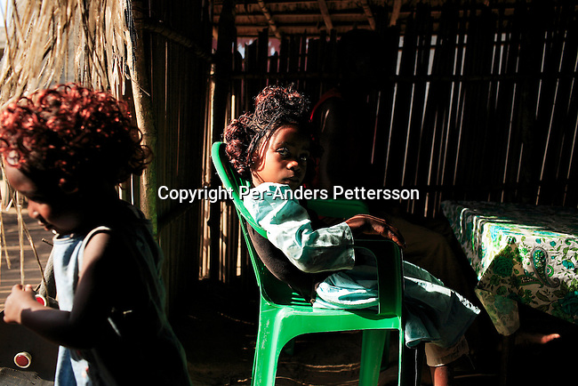 BUMBA, DEMOCRATIC REPUBLIC OF CONGO MARCH 25: Sefora Pasco (r), age 6, sits in a bar on March 25, 2006 in Bumba, Congo, DRC. She is one of about five hundred travelers on a boat traveling on the Congo River between Kisangani and Kinshasa, a journey of about 1750 kilometers. She travels with her father and family members to Kinshasa, the capital. The Congo River is a lifeline for millions of people, who depend on it for transport and trade. (Photo by Per-Anders Pettersson)..