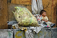 A little Colombian kid sits next to a sack of fresh corn in the 'Invasión', a temporary slum in Bogota, Colombia, 1 April 2006. The internal armed conflict in Colombia together with lack of social network caused appearence of small invasion slums in all Colombian urban zones in last years. These illegal settlements rise quickly in free uncontrolled spaces between industrial buildings, both in the city centres and peripheries. Shacks do not have sanitation network, neither electricity. Most of their inhabitants are war fugitives violently displaced from their original lands in the country by guerrilla or paramilitary forces. Picking up the rubbish and recycling it is a common survive strategy for people living in these temporal ghettos until those are not dismantled by city administration.