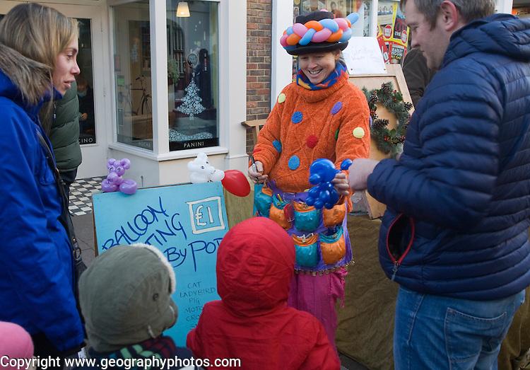 Woman shaping balloon animals for children during Christmas street fair, Woodbridge, Suffolk, England
