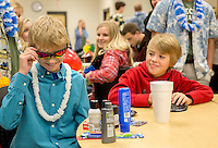 STAFF PHOTO JASON IVESTER --12/16/2014--<br /> Gunnison Riggins (left), 10, tries on his new sunglasses with his friend Eli Wisdom, 10, on Tuesday, Dec. 16, 2014, following a ceremony inside the Rogers High gym. With support from the school's DECA program, Gunnison's family was given a trip to Hawaii with the Make-A-Wish Foundation. Gunnison has been diagnosed with neuroblastoma.