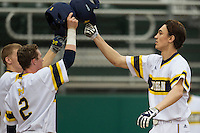 Michigan Wolverines outfielder Jackson Lamb (10) is greeted at the plate after his first inning home run in the NCAA baseball game against the Washington Huskies on February 16, 2014 at Bobcat Ballpark in San Marcos, Texas. The game went eight innings, before travel curfew ended the contest in a 7-7 tie. (Andrew Woolley/Four Seam Images)