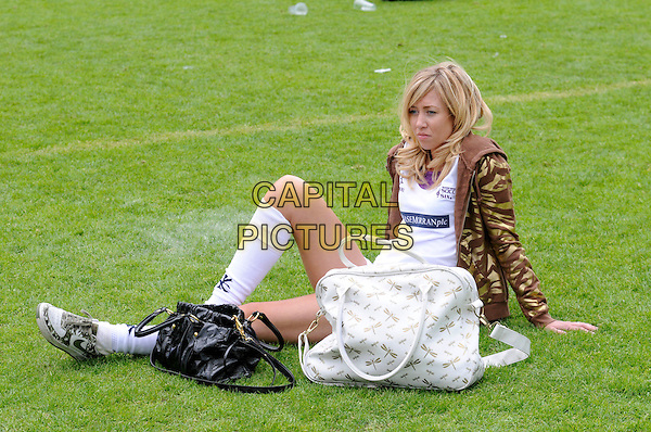 GRACE ADAMS-SHORT.The Music Industry Soccer Six charity football match, in aid of the Samaritans, held at Millwall FC's New Den ground, London, England. .May 18th 2008 .full length white socks sitting bags gold brown camouflage jacket .CAP/DH.©David Hitchens/Capital Pictures.
