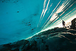 A traveler climbs below the Patagonian ice cap to peek at the rocks below.