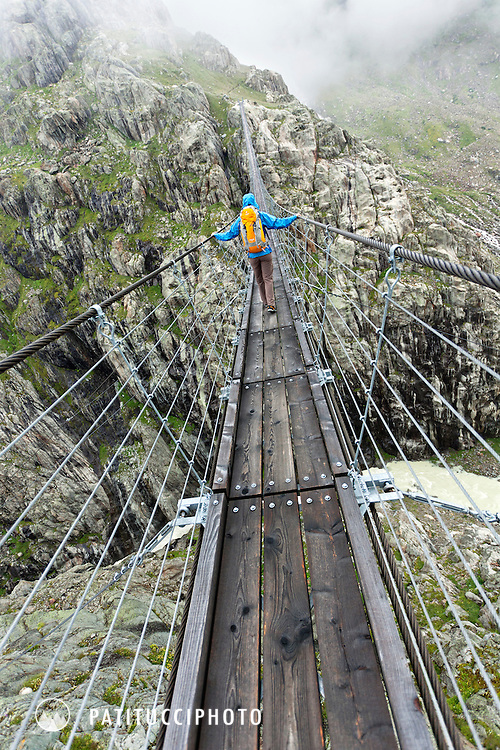 Female hiker crossing the Trift Bridge, the longest suspension bridge in Europe. Swiss Alps