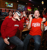 Nick Hart, right, and other Clemson football fans cheer as C.J. Spiller returns the game's opening kickoff for a touchdown while South Carolina fan Kevin Hughes watches at Wild Wing Cafe in Anderson.