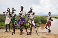 Ethiopia. Southern Nations, Nationalities, and Peoples' Region. Omo Valley. Korcho Village. Kara tribe. Agro-pastoralist group. A group of Kara warriors stand with their firearms, riffles and Kalashnikov, close to the Omo river. The Kara men are best known for the elaborate body painting they indulge in before important ceremonies. They paint their faces and bodies in white chalk and pierce their ears in five places. Scarification plays an important role in Kara body decoration. Every man carries a wooden headrest which doubles as a stool. The AK-47 (also known as the Kalashnikov, AK, or Kalash) is a selective-fire (semi-automatic and automatic) assault rifle. The Omo Valley, situated in Africa's Great Rift Valley, is home to an estimated 200,000 indigenous peoples who have lived there for millennia. Amongst them are 1,000 to 2,000 Karo who dwell on the eastern banks of the Omo river. Southern Nations, Nationalities, and Peoples' Region (often abbreviated as SNNPR) is one of the nine ethnic divisions of Ethiopia. 8.11.15 © 2015 Didier Ruef