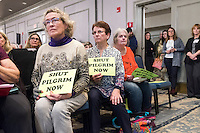 "Elizabeth Hogan, of Brewster, Mass., (left) holds a sign reading ""Shut Pilgrim Now"" at a public hearing regarding Pilgrim Station, a nuclear power plant run by Entergy, at Hotel 1620 in Plymouth, Massachusetts, USA, on Tues., Jan. 31, 2017. Hogan is a member of the Cape Downwinders, a group of area residents opposing the continued operation of Pilgrim Station. An email from the NRC was leaked in December 2016 outlining problems with the ""safety culture"" at the plant and an ""overwhelmed"" staff. Area residents have been calling for the plant to be shut down. The green signs in the audience, reading ""Shut Pilgrim Now,"" are from a group of area residents calling for the plant's closure called Cape Downwinders."