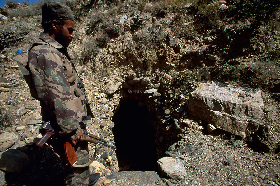 2004. Afghanistan. Montagnes de Tora Bora.Soldat de l'armee nationale afghane a l'entree d'une grotte qui jouxtait la derniere demeure localis&eacute;e de Ben Laden dans la montagne de Tora Bora.<br /> <br /> This cave in the Tora Bora Mountain is Bin Laden's last known house.