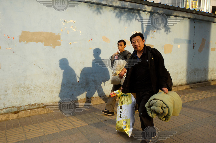 Migrants walk with their baggage having just arrived in the city.