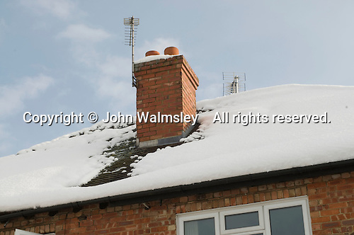snow; freezing; winter; suburban; snow scene; chimney; melting; Winter snow beginning to melt with heat from the chimney stack.