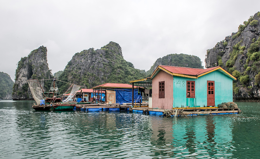 "A fishing village sits on the water in Vietnam's beautiful Ha Long Bay, which contains over 1,900 limestone ""karst"" islands projecting from the sea."