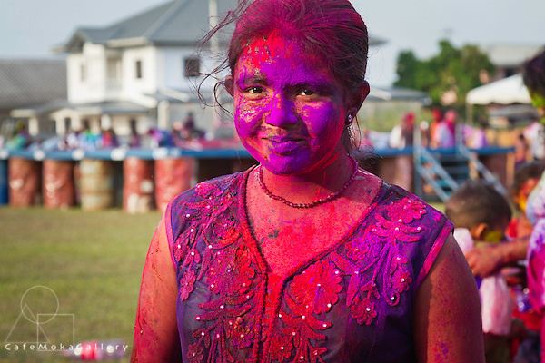 Smiling Trinidadian girl dressed in East-Indian clothes covered in red and purple dye - Phagwa or Holi