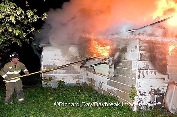 63818-021.03 Firefighter removing siding from burning house,  Marion Co. IL