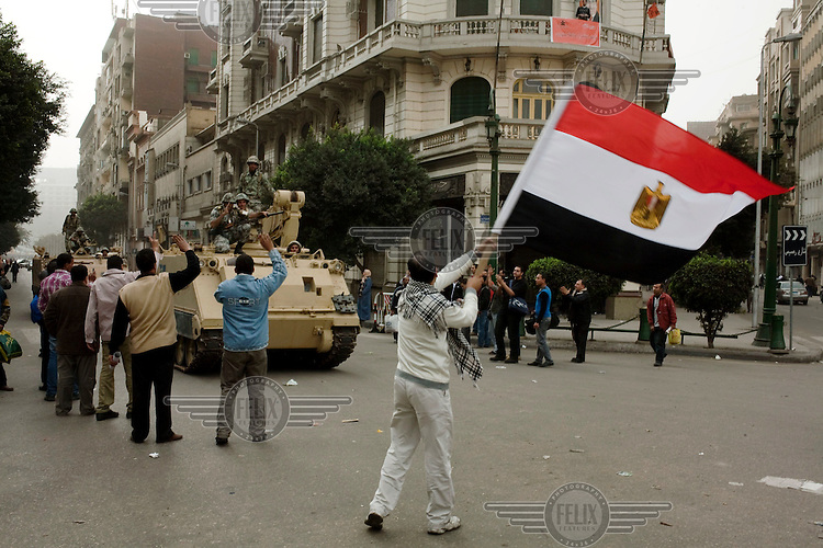 Protesters carrying an Egyptian flag march through the streets of central Cairo as tanks drive by. Continued anti-government protests take place in Cairo calling for President Mubarak to stand down. After dissolving the government, Mubarak still refuses to step down from power.