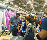 Workers from Voux speak to attendees at the TechDay New York event on Tuesday, April 18, 2017. Thousands attended to seek jobs with the startups and to network with their peers. TechDay bills itself as the U.S.'s largest startup event with over 500 exhibitors. (© Richard B. Levine)