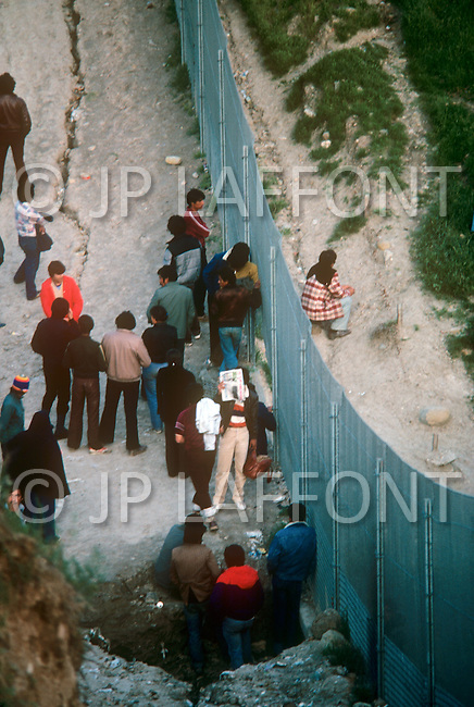 January, 1983. Tijuana, Mexico. At the border of Tijuana and San Diego, people are gathered on both sides, talking with eachother.
