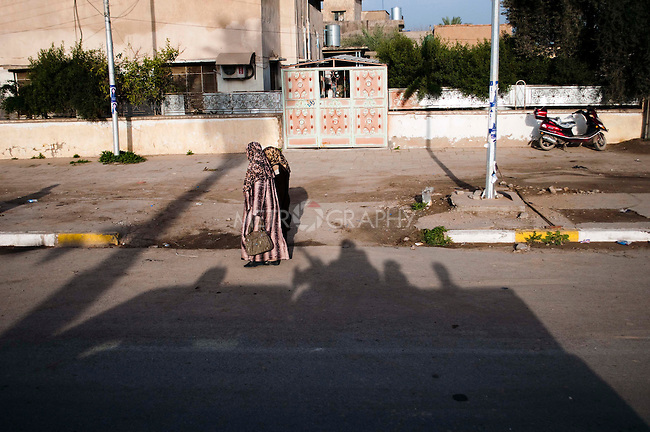 KIRKUK, IRAQ: A police truck casts its shadow at the feet of to woman on their way to vote...Residents of the city of Kirkuk vote for the first time.  Because of violence in the ethnically mixed city, Kirkuk was excluded from the 2005 elections...Photo by Kamaran Najm/Metrography