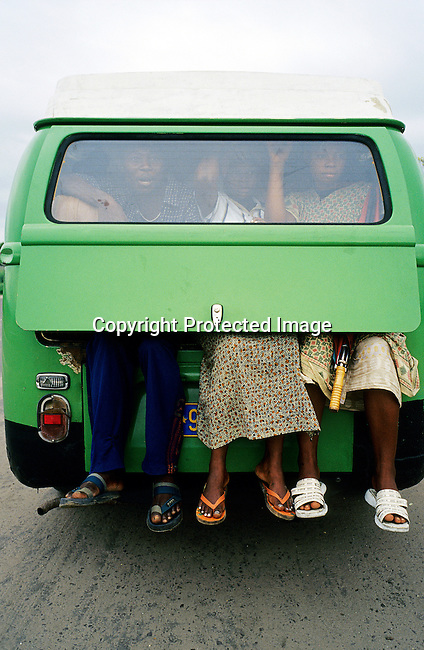 Passengers with their feet dangling out of the back of a Volkswagen kombi taxi on February 28, 2002 in Kinshasa, Congo. The Congolese economy and infrastructure is in total disarray after 40 years of independence from Belgium. The former strongman Mobuto Sese Seko fleeced the country and he died in exile in 1997. Corrupt people in he government stole a lot of the foreign aid and royalties from minerals. (Photo by: Per-Anders Pettersson)