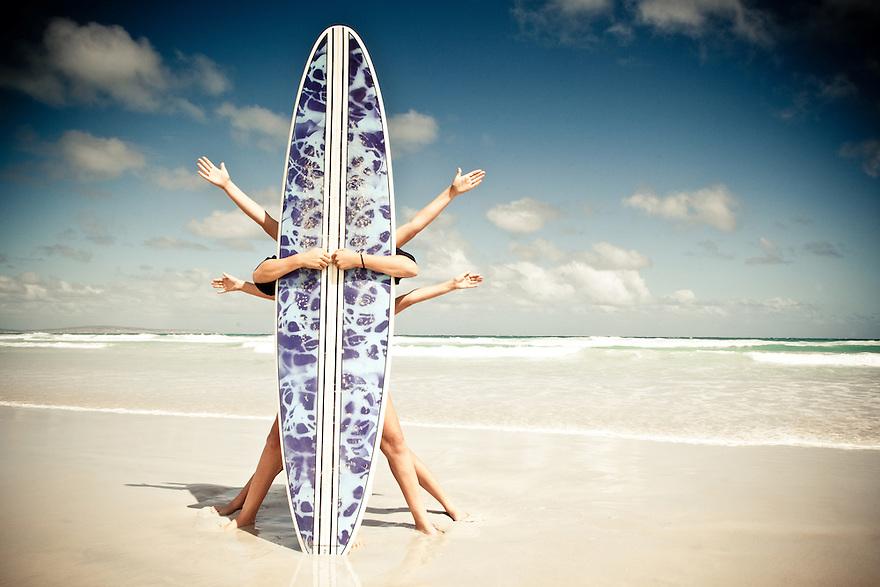 Three teenagers behind a surfboard.