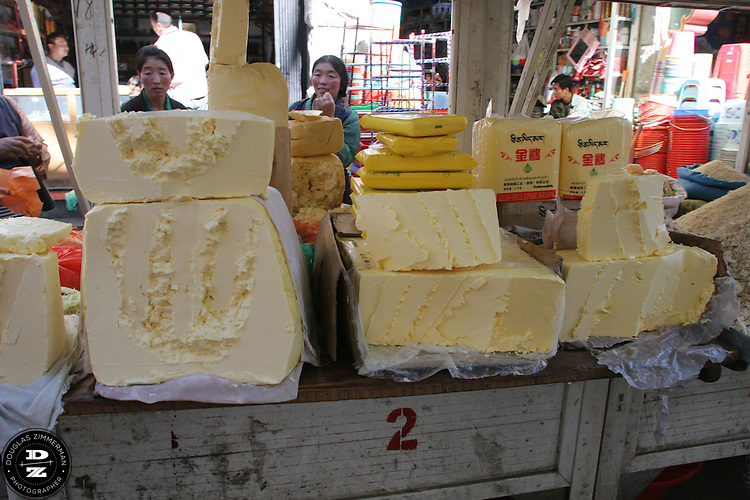 Merchants sell large stacks of yak butter at an outdoor market in the Barkhor area of Lhasa, Tibet.  Yak butter is the essential ingredient to make Tibetan tea, which consists of yak butter mixed with salt, milk, soda, tea leaves and hot water.   Photograph by Douglas ZImmerman
